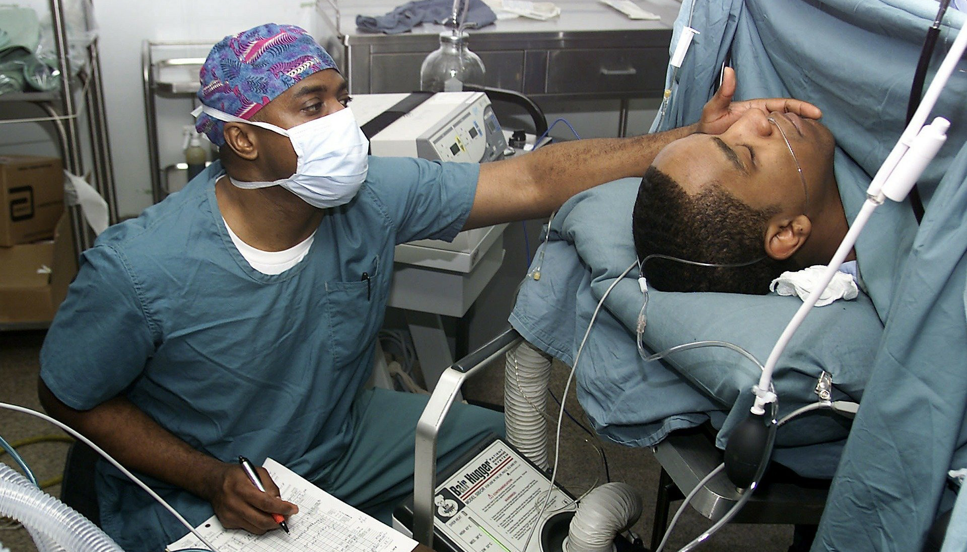 Anesthesiologist sitting by the head of a patient who is sedated in an operating room.